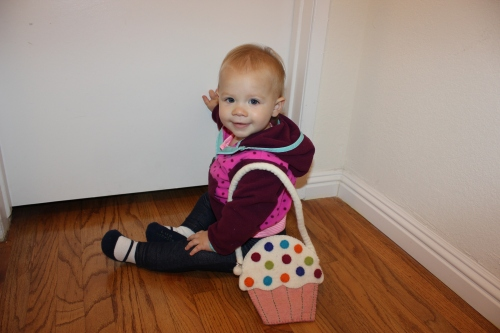 Wearing her The North Face jacket from Nana and playing with her cupcake purse